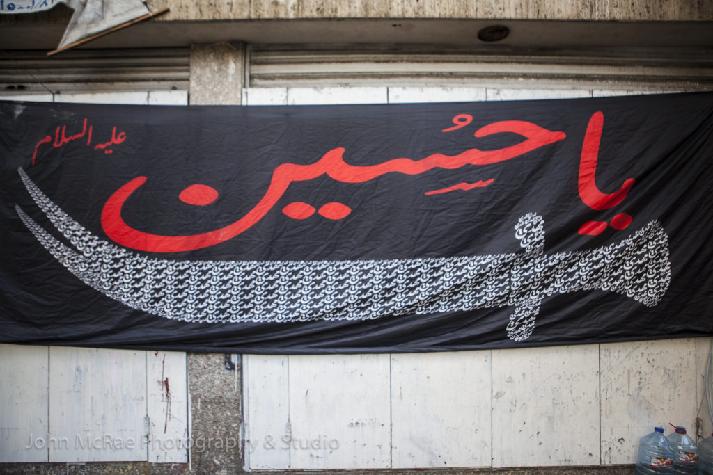 "The Shia festival, Ashoura, celebrates the matyrdom of Hussein (son of Ali, grandson of the Prophet Muhammad).  He died in the battle of Karbala in 680 AD.  Many flags and banners are displayed around the city.  Above is ""Ya Hussein"", written in Arabic.  ©johnmcrae"